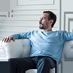 Mann sitzt auf Sofa zur Sitzprobe