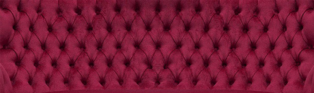 Rotes Sofa mit Rautenheftung.